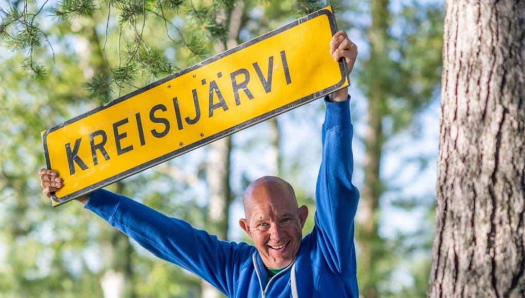 """Nauravainen sinipaitainen mies pitelee pään yläpuolellaan keltaista kylttiä, jossa lukee """"Kreisijärvi"""". Taustalla vihreikköä kesäisessä säässä."""