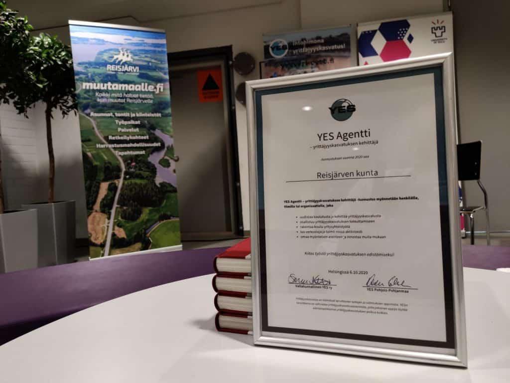 Kuvan etualalla, pöydällä YES-verkoston myöntämä YES Agentti -tunnustus Reisjärven kunnalle. Taustalla muutamaalle.fi-kyltti.
